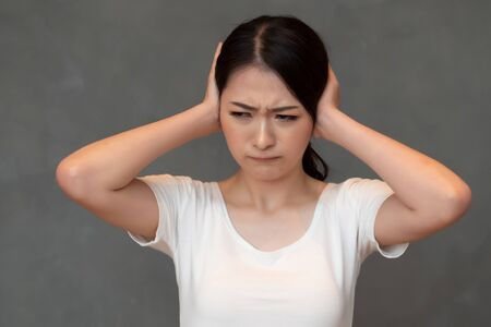 woman do not want to listening to something; portrait of asian woman covering her ear, concept of rumor, gossip, fake news, bad news, inconvenient truth, lie, scam, depression Stok Fotoğraf