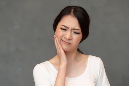 woman with toothache; sick asian woman suffering from toothache, tooth decay, tooth sensitivity, wisdom tooth pain, cavity, dental care concept; young adult asian woman model Stock fotó
