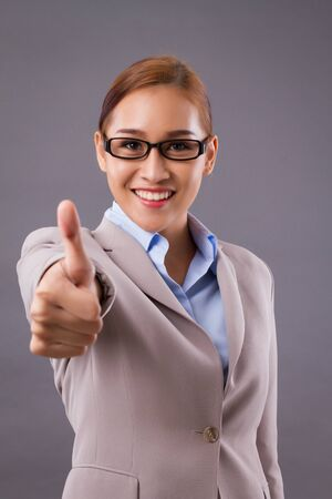 happy smiling business woman pointing thumb up gesture; concept of good deal, fine business, yes answer, deal maker, acceptance, approval