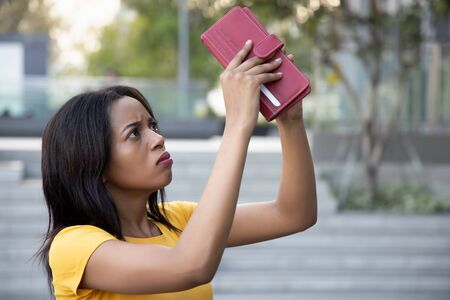 African woman without money; portrait of poor black African woman with empty wallet, poor people, poverty, bankruptcy, financial broke, unemployment, joblessness; no credit, no money concept