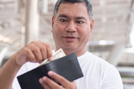 old senior man having some money in his wallet; concept of money revenue, wages, economic growth, job, employment, financial plan, expenditure, cost of living