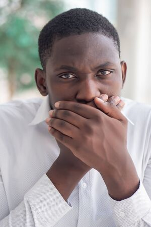 African black man covering his mouth; African black man displaying concept of censorship, free speech limitation, no free speech, secret, news manipulation, hidden truth, problem cover up