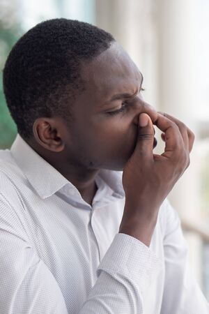 African black man covering his nose for bad smell; African black man plugging his nose to display concept of bad smell, bad breath, dirty or filthy thing, rotten stuff, gross fart smell