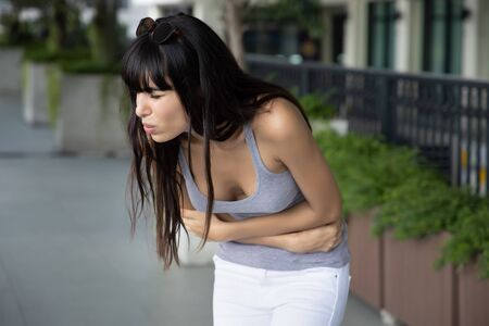 Hispanic woman having stomachache, suffering from belly pain, abdominal pain, period cramp, menstruation cramp, menstrual abnormality, flatulence gas, indigestion, diarrhea, constipation