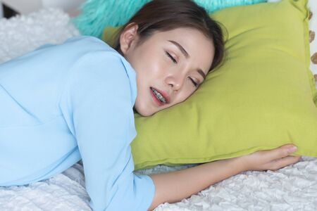 one woman sleeping on bed at home; asian woman alone sleeping for concept of rest at home, resting, social distancing, physical distancing, stay home, self isolation, new normal Standard-Bild