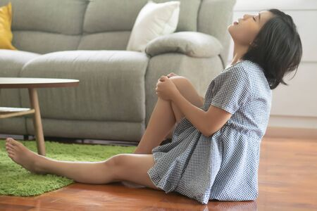 injured woman falling down with slippery floor causing knee pain or leg injury; portrait of Chinese asian woman having knee pain; concept of wound, bruise, injury, scratch, pain from home accident