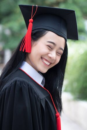 happy smiling college student graduating looking up; concept of successful education, happy commencement day, woman education opportunity, graduation, education vision, overseas study scholarships