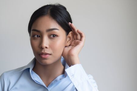 woman listening to something; portrait of southeast asian woman with hearing ear, concept of rumor, gossip, hearing loss, whispering, hard of hearing, fake news, good news, bad news