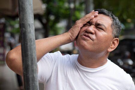 unlucky careless old senior man hitting his head with iron pole; concept of head injury, head accident, brain injury, brain lesion, memory loss, amnesia; asian senior man model Stock Photo