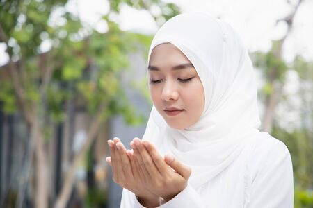 Muslim woman in hijab & middle eastern dress praying with islamic faith; concept of Muslimah, Namaz woman, islamic faith, muslim meditation, Ramadan Kareem, Ramadan Mubarak, Eid Kareem, Eid Mubarak