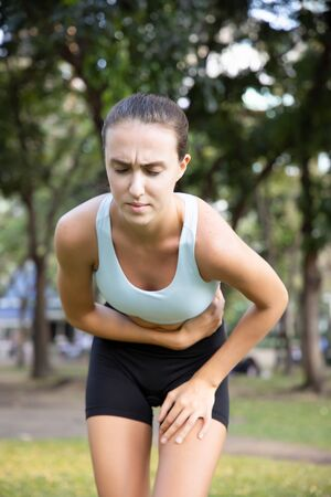 sports woman, fitness woman suffering from stomachache, diarrhea, constipation, food poisoning Stockfoto