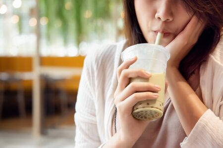 happy young asian woman drinking boba milk tea, bubble milk tea, pearl milk tea