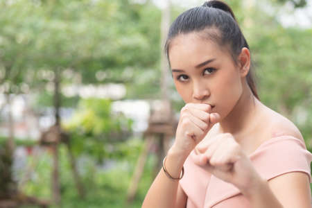 asian woman assuming defensive guard stance with street fight self defense