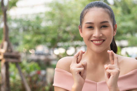 woman wishing, praying for luck with finger crossed gesture