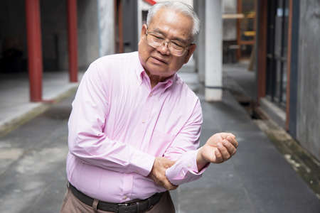 Sick old senior man suffering from elbow joint pain