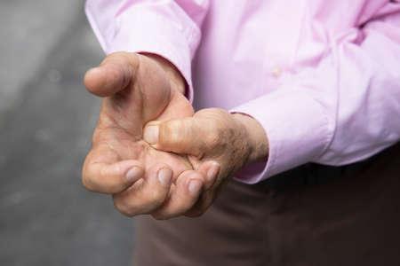 Old senior man suffering from trigger finger