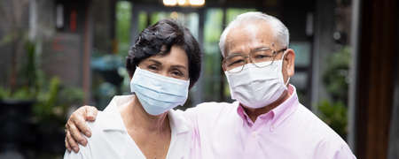 senior asian couple wearing face mask or face covering, concept social distancing, new normal lifestyle, protective health care; banner format