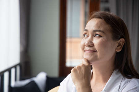 happy middle aged woman thinking, looking up 免版税图像
