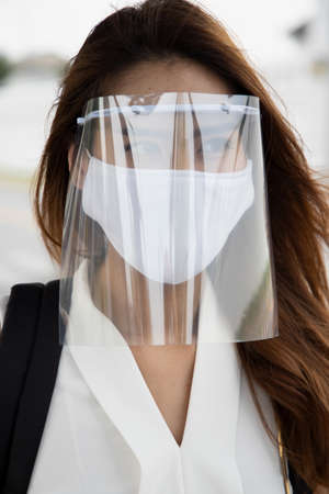 woman wearing face mask and face shield, observing new normal social distancing measure to flatten the curve and prevent virus infection by taking extra physical distance precaution