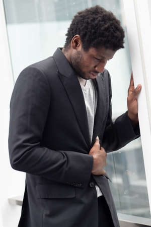 Upset stressed African black businessman having stomachache, portrait of failed unhappy black business man, concept of work problem, office stress syndrome, economic recession, layoff, unemployment