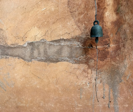 rustic: Rustic yellow wall with copper bell