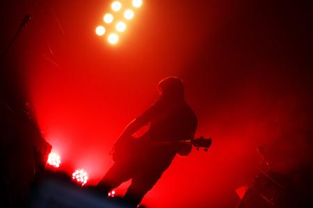 croud: Black silhouette of guitarist at rock concert