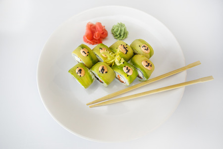 exotically: Japanese  seafood  sushi , roll and chopstick on a white plate with ginger and wasabi