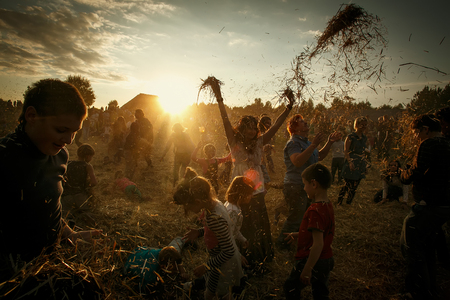 Playing with hay with hay for Fall decoration at market place, country festival, sunset, fest Minsk, Belarus
