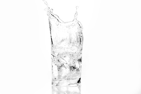 fill up: Ice cubes splashing into glass of water, isolated on white