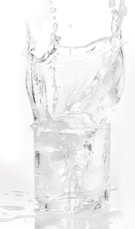 bleb: Ice cubes splashing into glass of water, isolated on white