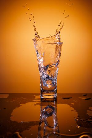 反射とオレンジ色の背景上の水のガラスにしぶき氷