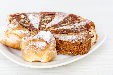 tort: carrot cake with walnuts, prunes and dried apricots on white wood background