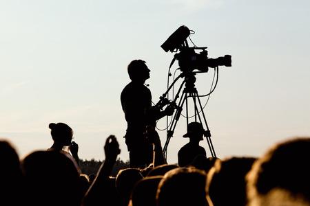 silhouette of cameraman operator shooting a live rock concert, fans around raised hands Banco de Imagens - 62738218