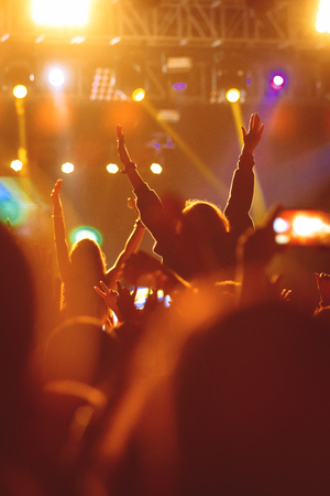 Black silhouette of young girl on rock concert, raised hand