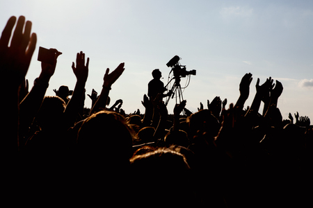 cameraman: silhouette of cameraman operator shooting a live rock concert, fans around raised hands Stock Photo