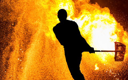 Fireshow performance. Silhouette of man with hammer, fire around Stock Photo