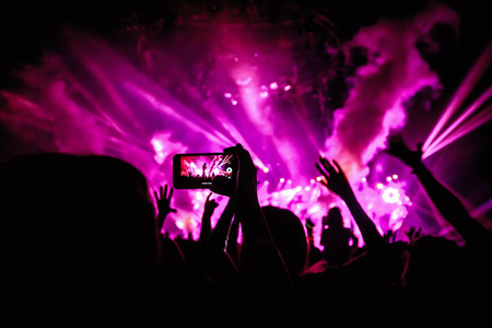 Hand with a smartphone records live music festival, Taking photo of concert stage, live concert, music festival, happy youth, luxury party, landscape exterior - purple light Reklamní fotografie - 63676818
