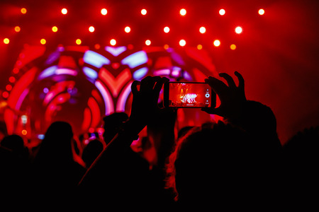 live happy: Hand with a smartphone records live music festival, Taking photo of concert stage, live concert, music festival, happy youth, luxury party, landscape exterior - purple light