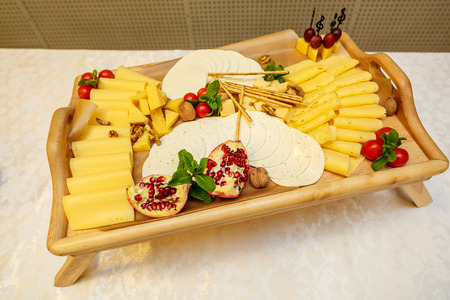 tabla de quesos: Cheese plate with variety of appetizers on table on event catering