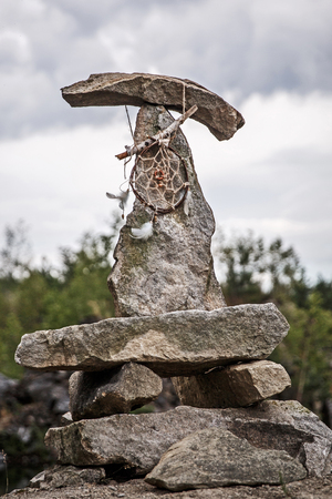 lucky charm: Dreamcatcher on a pyramid of stones, Dramatic clouds around