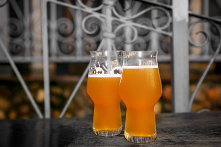 Two glasses of beer on a table in a street cafe, selective focus Stock Photo