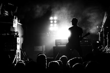 Silhouette des Gitarristen in Aktion auf Konzertbühne, schwarz und weiß