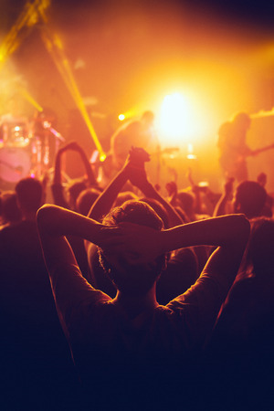 Rock concert, cheering crowd in front of bright colorful stage lights, Hands behind the head with pleasure from the show