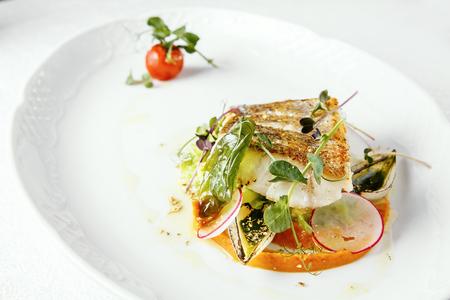Fish dish - fried fish fillet of zander served with tomato, Radish and milk sauce