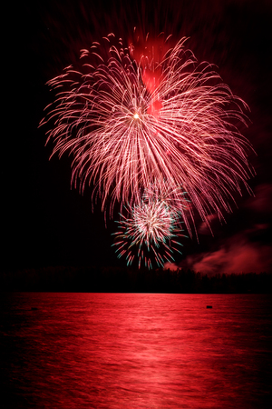 Red firework in a night sky, reflection in water Stock Photo