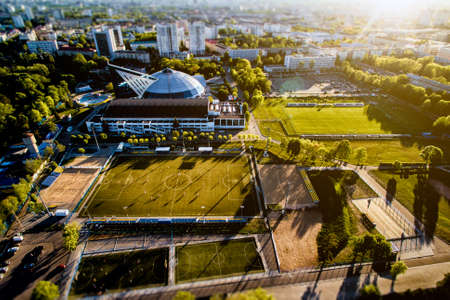Top view from the drone to the sports grounds, football field in the city, sunset Stock Photo
