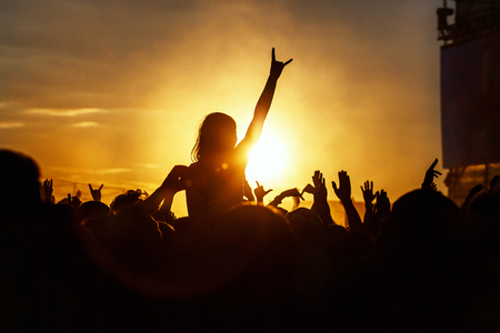 Young girl enjoys a rock concert, Silhouette on sunset, hands up on openair Stockfoto