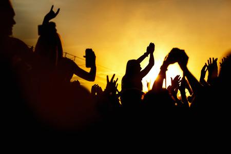 aplaudiendo: Young girl enjoys a rock concert, Silhouette on sunset, hands up on openair Foto de archivo