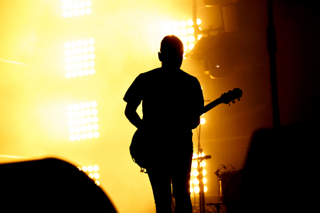 Silhouette of guitar player, guitarist perform on concert stage. Orange background, smoke, concert spotlights. Stock Photo