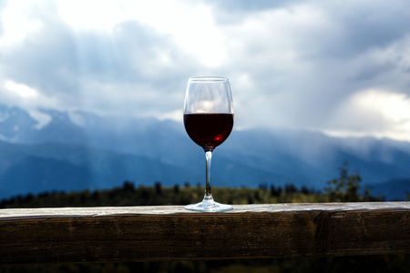 Glass of red wine and mountains on background